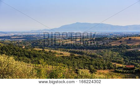 Overlook of a tuscan field and hills and Monte Argentario in Italy