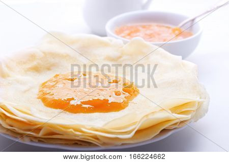 Crispy crepes with apricot jam served on a table