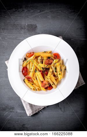 Penne with anchovy and tomato on a wooden surface
