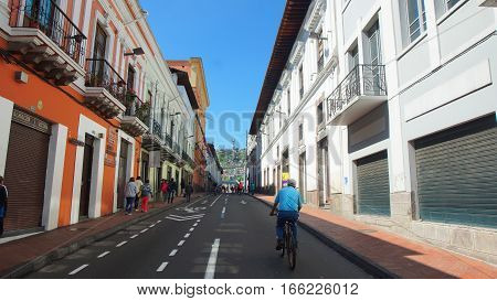 Quito, Pichincha / Ecuador - January 22 2016: Man walking on a bicycle in the Historic Center of Quito. The historic center was declared by UNESCO the first Cultural Heritage on 1978