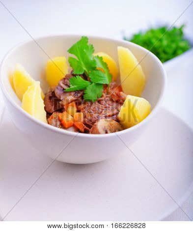 Beef stew being in a slow cooker, garnished with potatoes and carrots.