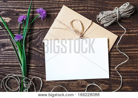 Blank white greeting card and envelope with purple wildflowers on brown rustic wood background for creative work design. flat lay