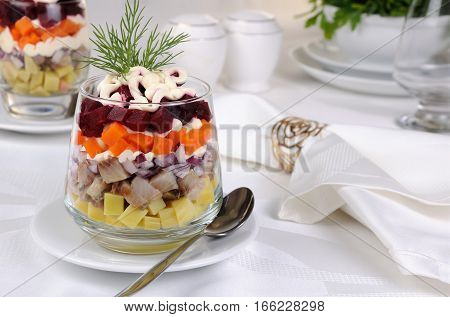 Salad of chopped herring with onions potatoes beets carrots seasoned with yogurt sauce in a glass