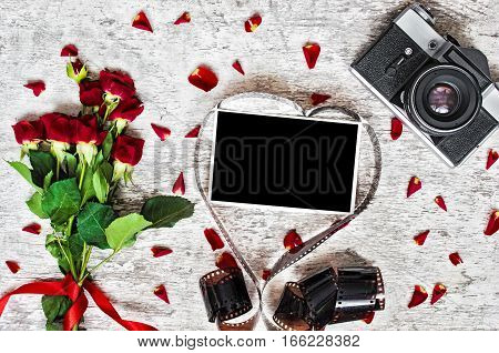 blank photo frame in heart shape made from film with vintage retro camera and bouquet of red roses and gift box. valentines day background. top view