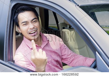 Portrait of angry businessman showing middle finger while driving a car on the road