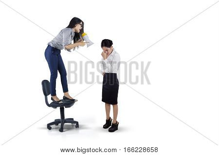 Picture of angry businesswoman shouting to her subordinate with megaphone while standing on the chair isolated on white background