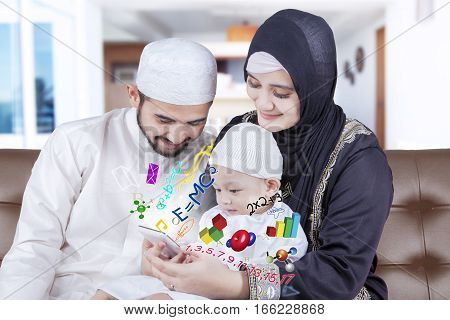 Arabian parents giving education to their cute son by using a smartphone while sitting on the sofa
