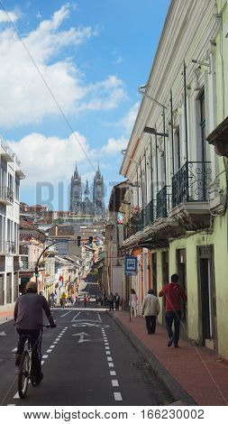 Quito, Pichincha / Ecuador - January 22 2016: People walking on a bicycle in the Historic Center of Quito with the Basilica of the National Vow in background