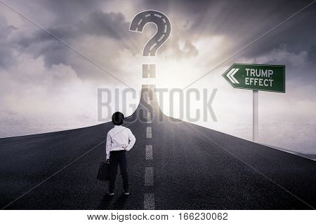 Rear view of little boy standing on the road turning into a big question mark with Trump Effect word on the signboard