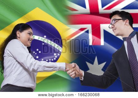 Image of attractive Brazilian businesswoman shaking with Australian businessman in front of Brazilian and Australian flags