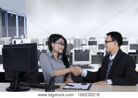 Young businessman giving a congrats sign by shaking hands on new employee with a computer and a document on the desk