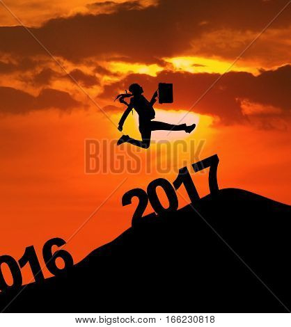 Businesswoman carrying suitcase while leaping on the mountain above numbers 2017 in the sunset