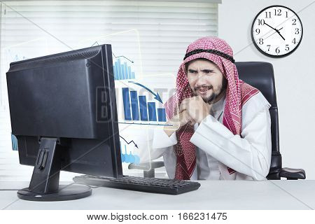 Portrait of young male entrepreneur wearing Muslim clothes while looking at the virtual decline graph on the monitor and sitting in the office