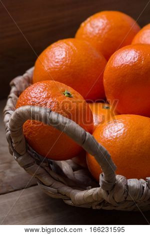 Several ripe tangerines in a wicker basket. Wooden background. Close-up