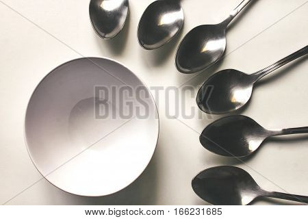 Set of table spoons and a white plate are laid out on a white table