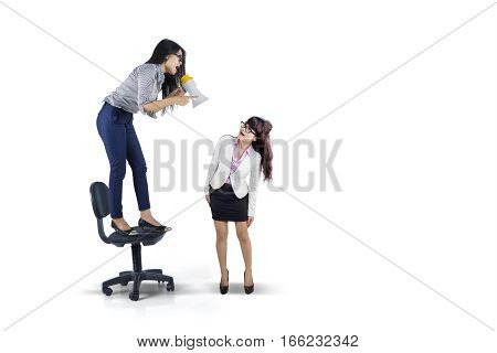 Picture of young entrepreneur shouting to her subordinate by using a megaphone isolated on white background