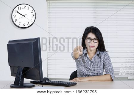 Picture of a female worker pointing finger at you while wearing glasses and looks angry in the office
