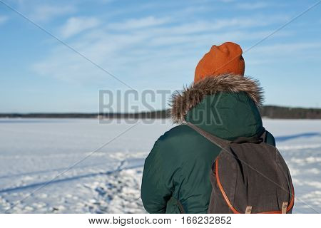 Back view on backpacker man in green winter jacket and red hat with backpack. Free space for advertising travaler goods. Free horizont with blue sky and white light clouds in sunny day.