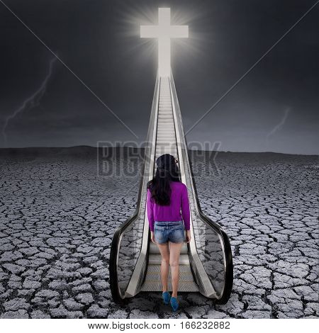 Teenage girl walking on a drought land toward the heaven through a stairway