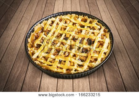 Image of homemade apple pie in baking dish on the wooden table