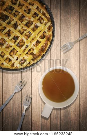 Top view of yummy apple pie with a cup of hot tea and forks on the wooden table