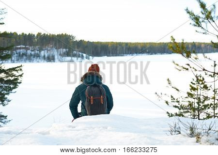 Back view on nature tourist in green jacket and orange hat. Man sit on high point of view and look on the frozen forest lake. Free space for advertising goods or text.