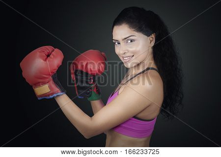 Image of attractive Indian boxer looking at the camera while posing ready to strike on black background