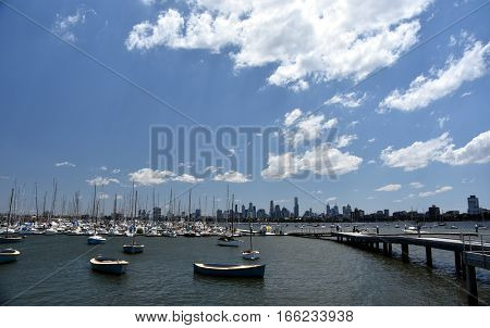 Melbourne skyline from St Kilda (Victoria Australia). View from a wooden jetty over the city of Melbourne in the Port Phillip Bay in Victoria and many yachts on the quay.