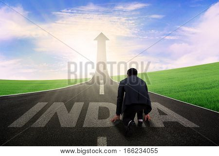 Image young male entrepreneur kneeling on the road and ready to chase success in the Indian country