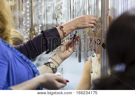 Customers in the store choosing jewelry items. Sale