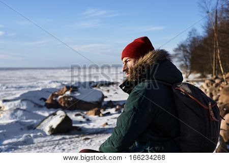 Serious 30 years bearded man in green jacket with hipster backpack sit on the beach of frozen sea and thinking. Portrait of traveler in orange hat. Copy space for advertising or place goods.