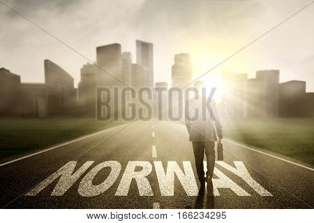 Image of male manager holding a briefcase and walking above Norway word on the road