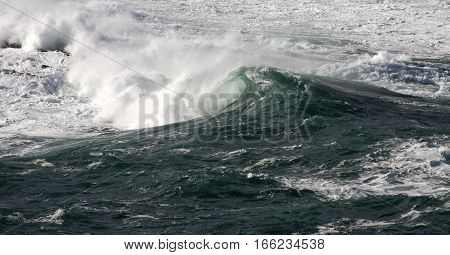 Wave breaking, bottle green colors and white foam