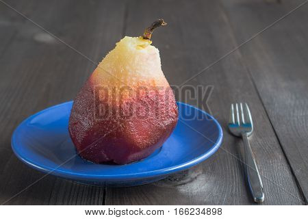 one poached pear on blue little dish plate with fork on dark wooden background