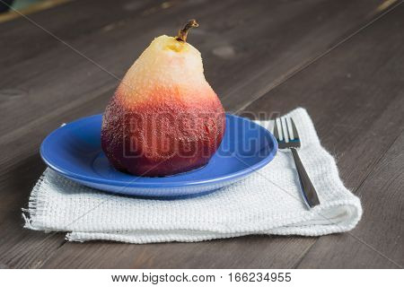 one poached pear on blue little dish plate with fork on white towel napkin dark wooden background