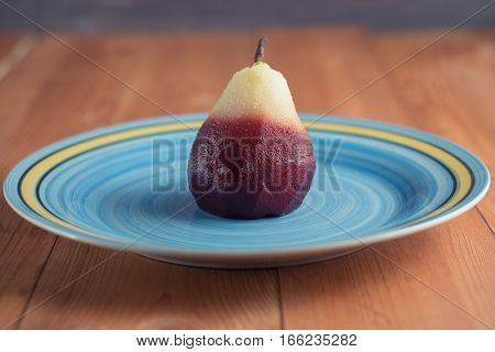 one poached pear on blue big dish plate on wooden background