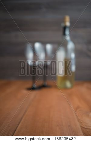 blurred image with two wine glasses and bottle of white wine. wooden background. selective focus. out of focus image