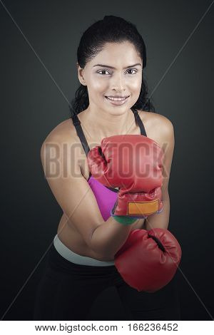 Portrait of female boxer in an attack stance with red boxing gloves looking at the camera on black background