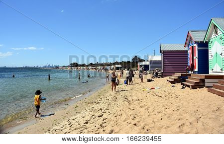 Melbourne Australia - December 30 2016. People swimming on Brighton Beach (Victoria Australia). Colourful bathing boxes on the beach. View over the city of Melbourne in the Port Phillip Bay.
