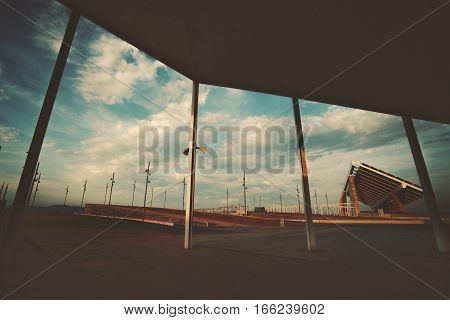 Wide angle shoot through beams of modern contemporary asphalted area with for extreme sports recreation and parkour in Barcelona Forum district sunset huge solar station in distance