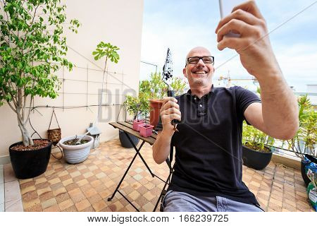 Adult man planting tomatoes on his balcony, taking selfies to post online.