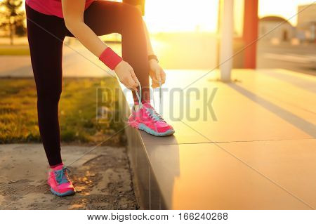 Female runner tying shoe lace in a urban area. Healthy lifestyle.