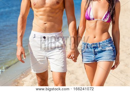 Close Up Of Slim Fit Masculine Couple Walking On The Beach. Young Family Resting