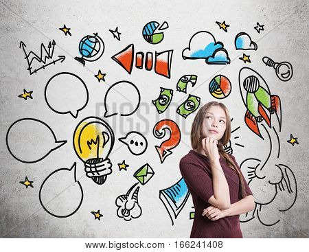 Portrait of a girl with braided hair wearing a red dress who is standing near a concrete wall with colorful start up icons drawn on it.
