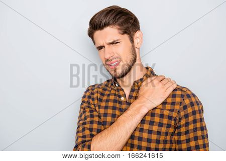 Portrait Of Sad Young Man Suffering From Ache In Shoulder