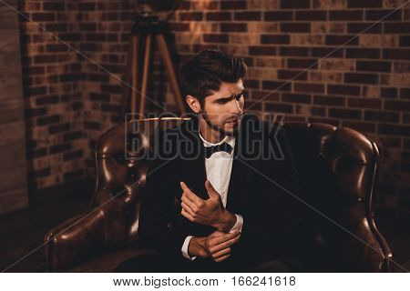 Portrait Of Young Groom Sitting On Sofa And Fastening Buttons On The Sleeves
