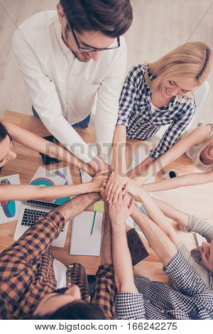 Top view of group of young people holding hands together