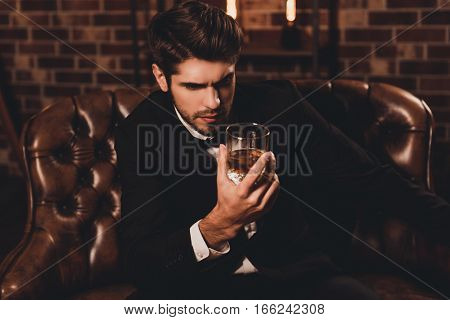 Portrait Of Handsome Young Man Holding Glass Of Cognac