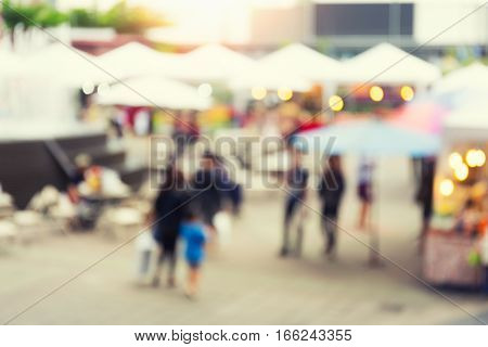 Blurred photo of food exhibition fair with many people at twilight time for background.