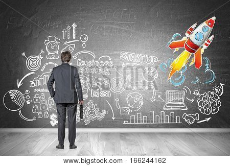 Rear view of a businessman looking at a business strategy sketch drawn on a blackboard. There is a colorful rocket icon in the corner.